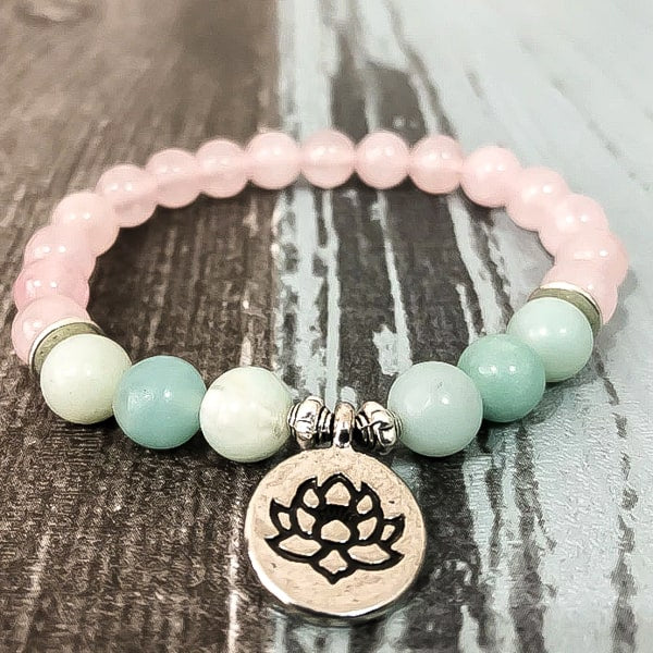 Beaded lotus flower charm bracelet displayed close up on a wooden background