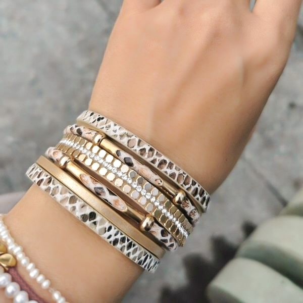 Woman wearing a beige and gold snakeskin leather cuff bracelet on her wrist