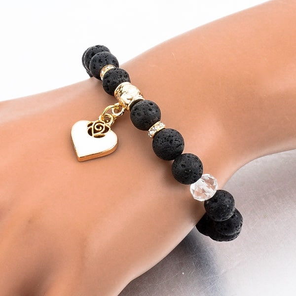 Woman wearing a beaded lava stone bracelet with a gold heart charm