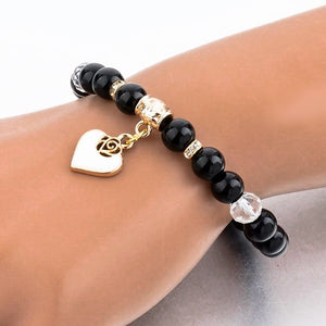 Woman wearing a beaded black obsidian bracelet with a gold heart charm