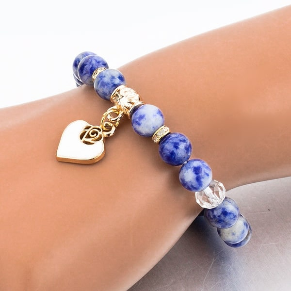 Woman wearing a beaded blue sodalite bracelet with a gold heart charm