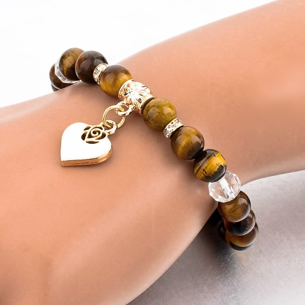 Woman wearing a beaded brown tiger eye bracelet with a gold heart charm