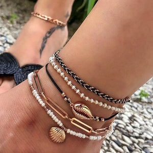 Cowrie and seashell anklet set on a womans ankle