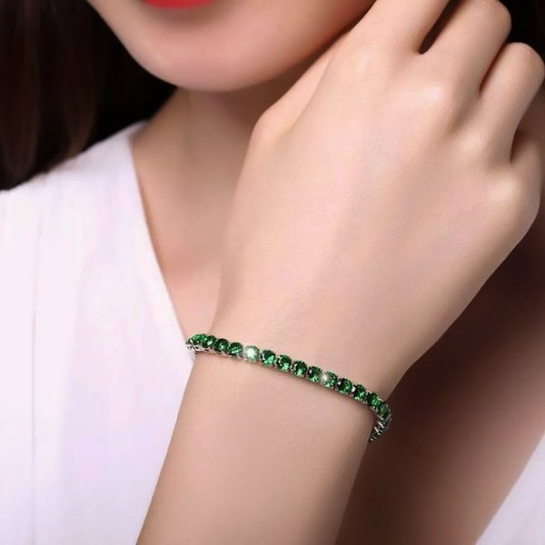 Emerald green cubic zirconia tennis bracelet on a woman's wrist