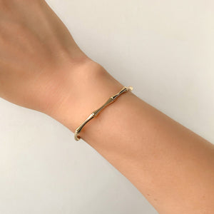 Woman wearing a gold bamboo cuff bracelet on her wrist