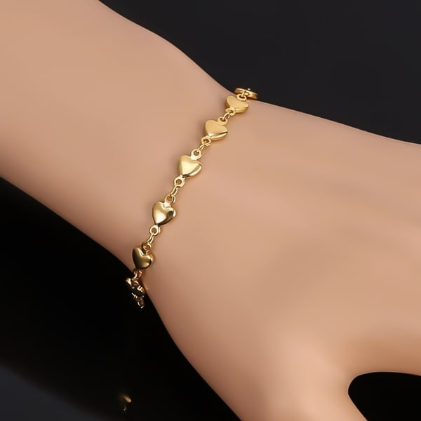 Woman wearing a gold heart chain bracelet on her wrist