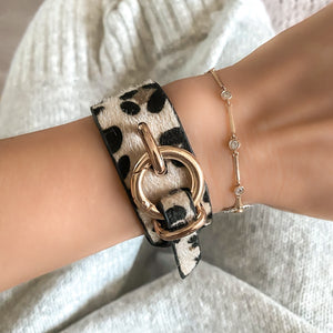 Woman wearing a leopard bracelet with gold fashion clasp