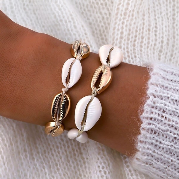 Gold and white cowrie shell bracelet on a woman's wrist