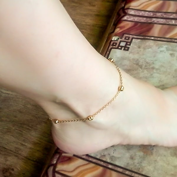 Gold dainty beaded chain anklet on a womans ankle