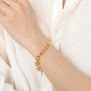 Gold designer cable chain bracelet on a woman's wrist