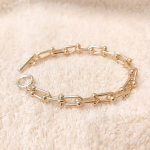 Gold designer link chain bracelet displayed on a white furry background