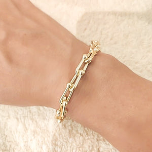 Gold designer link chain bracelet on a woman's wrist