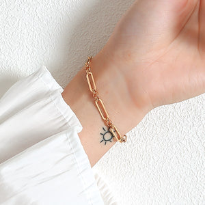 Gold designer oval link chain bracelet on a woman's wrist