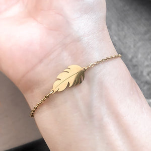 Gold feather bracelet on a woman's wrist