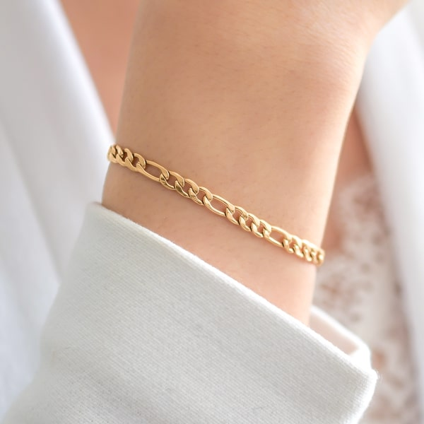 Gold figaro chain bracelet on a woman's wrist
