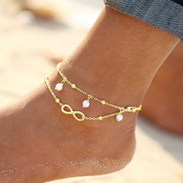 Gold infinity ankle bracelet worn on an ankle