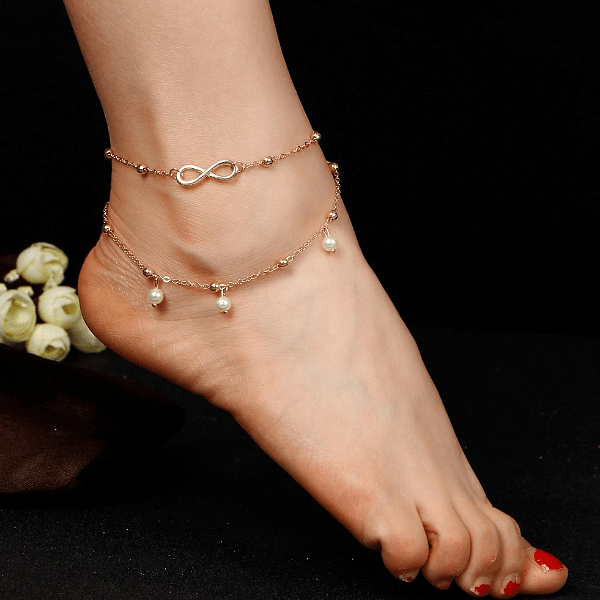 Gold infinity ankle bracelet worn on an ankle with a dark background