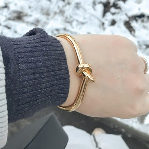 Gold knot cuff bracelet on a woman's wrist