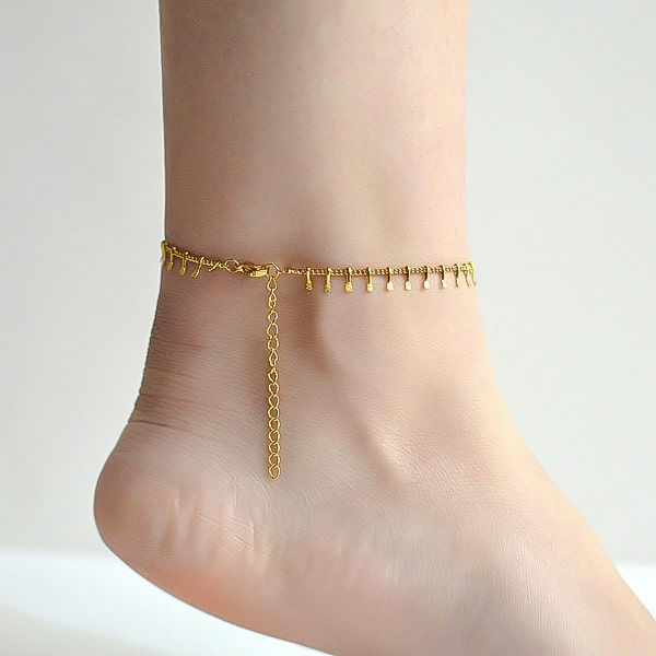 Gold lucky charm anklet on a woman's ankle