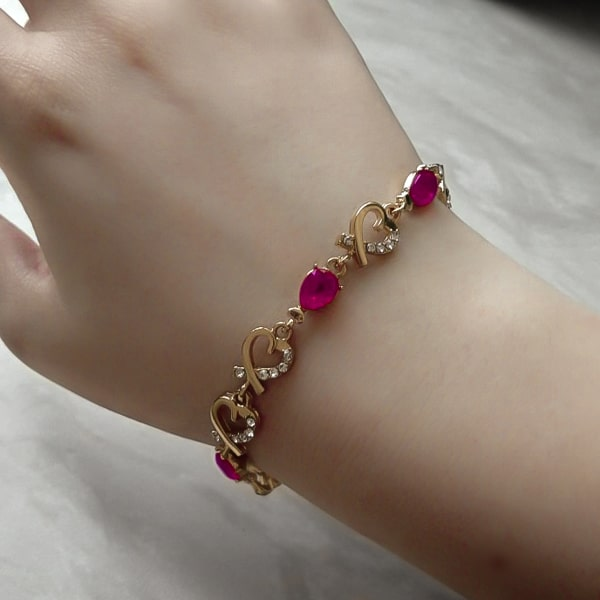 Gold heart chain bracelet with purple crystals on a woman's wrist