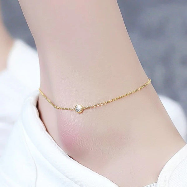 Gold simple crystal anklet displayed on an ankle