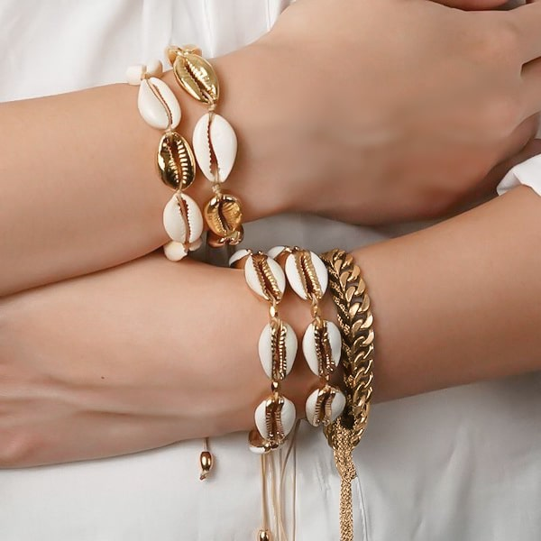 Golden cowrie shell bracelet on a woman's wrist