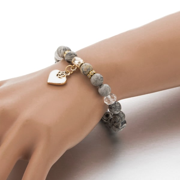 Woman wearing a beaded grey onyx stone bracelet with a gold heart charm