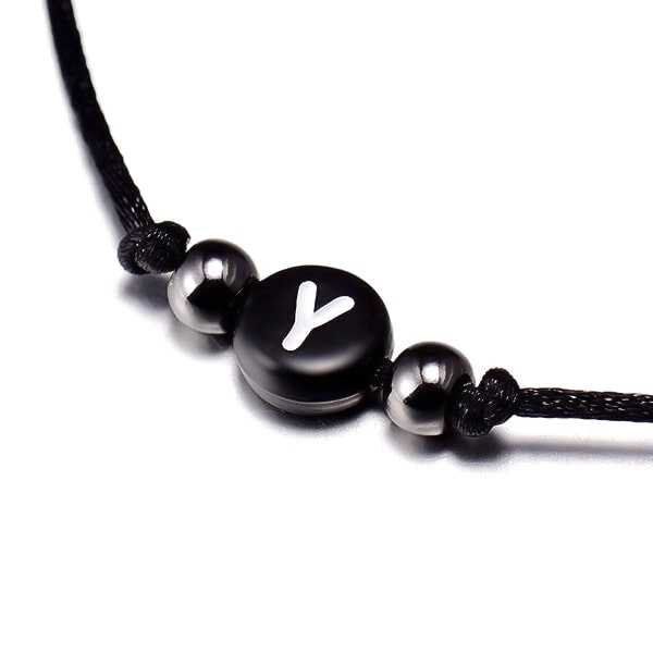 A black initial letter bead on an adjustable macrame bracelet