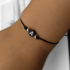 A black initial letter bracelet on a womans wrist