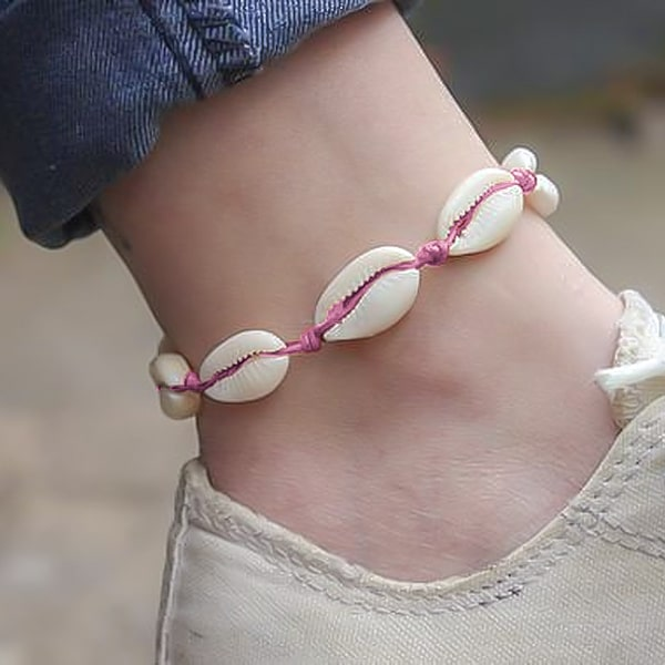 Pink cowrie shell anklet on a womans ankle