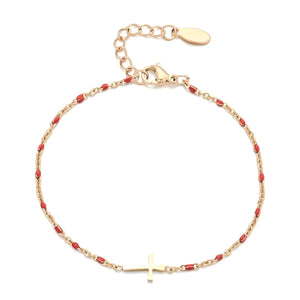 Gold cross bracelet with red beads