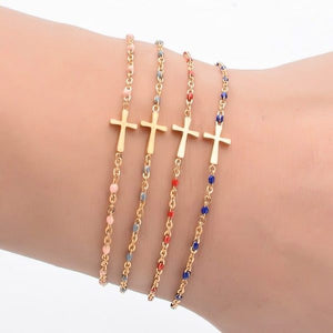 Woman wearing a gold cross bracelet with red beads