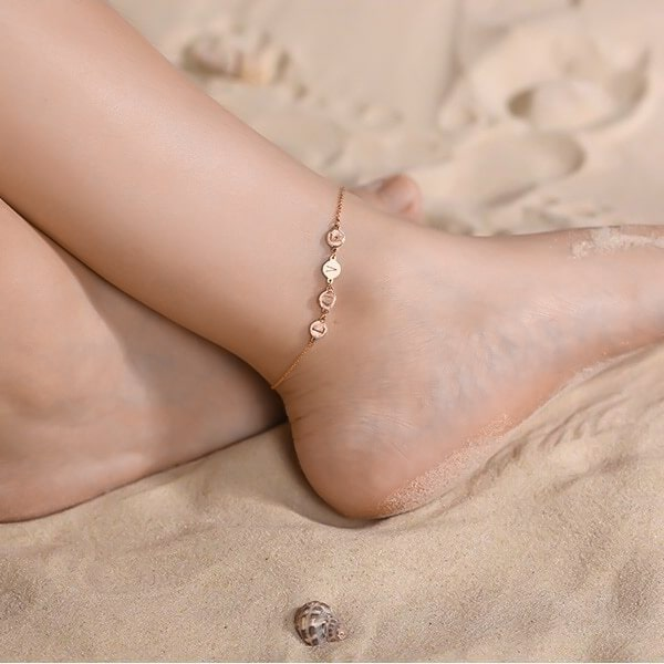Woman wearing a rose gold love ankle bracelet