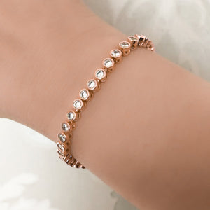 Woman wearing a rose gold round tennis bracelet on her wrist