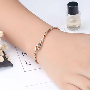 Rose gold angel wing bracelet on a woman's wrist