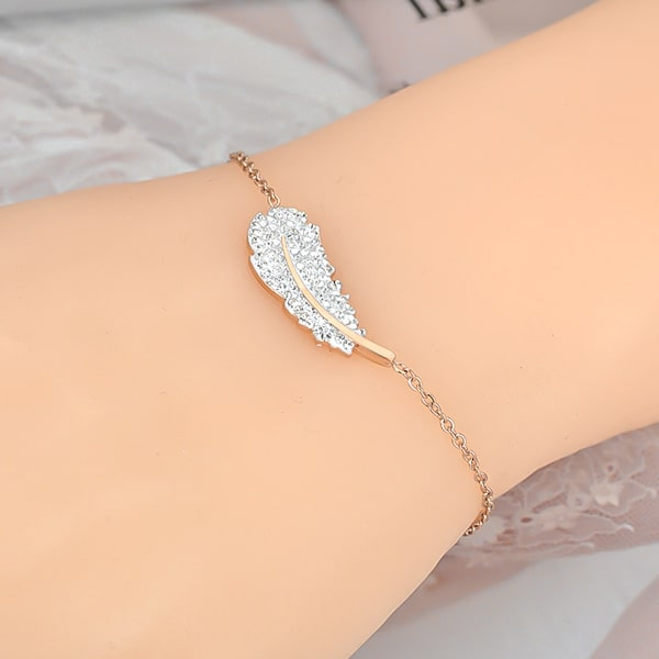 Rose gold crystal feather bracelet displayed on a woman's wrist