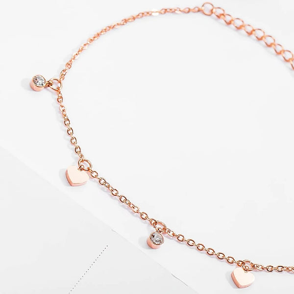 Rose gold love charm anklet with heart and crystal pendants close up