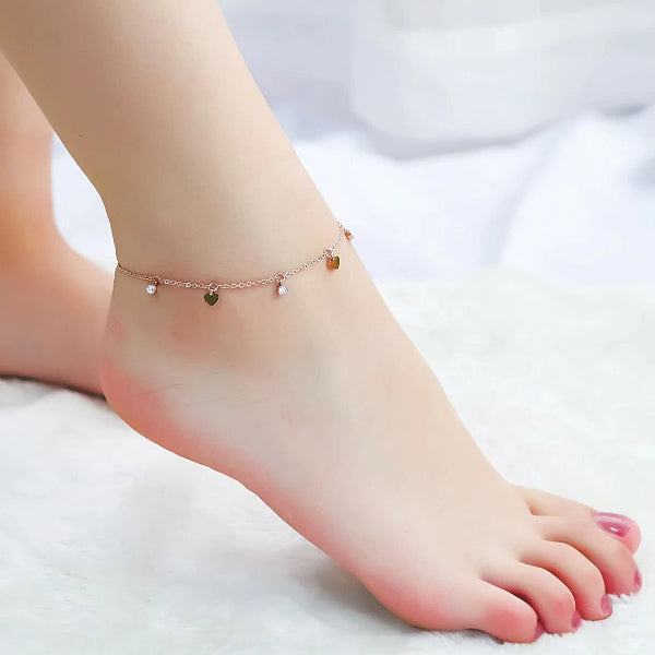 Rose gold love charm anklet with heart and crystal pendants displayed on an ankle