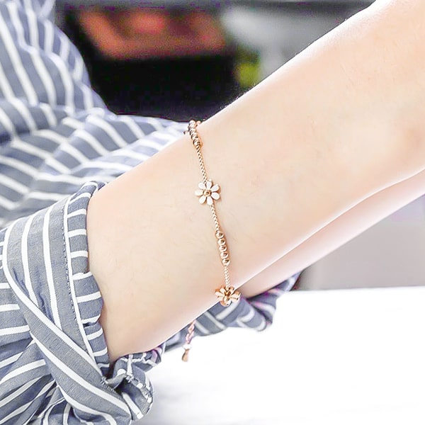 Rose gold daisy flower bracelet on a woman's wrist
