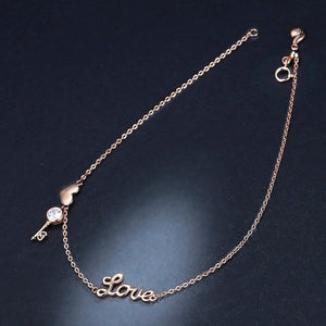 Rose gold vermeil love ankle bracelet on a dark background