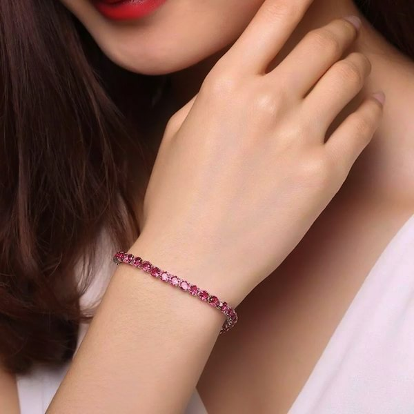Ruby red cubic zirconia tennis bracelet on a woman's wrist