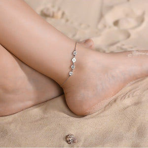 Woman wearing a silver love ankle bracelet