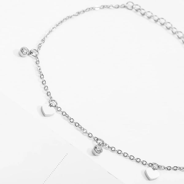 Silver love charm anklet with heart and crystal pendants close up