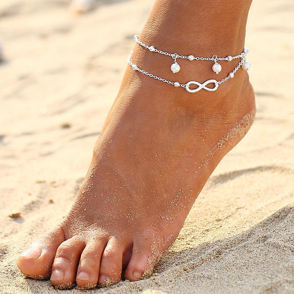 Silver infinity ankle bracelet worn on an ankle