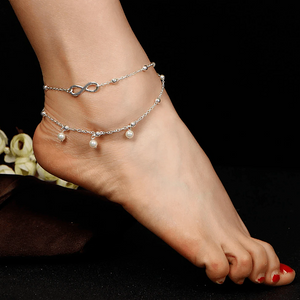 Silver infinity ankle bracelet worn on an ankle with a dark background