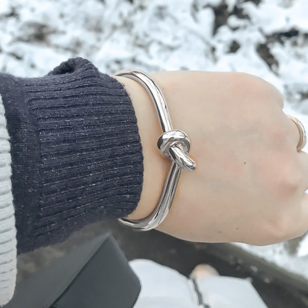 Silver knot cuff bracelet displayed on woman's wrist