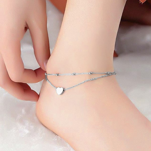 Silver layered beads and heart anklet on a womans ankle