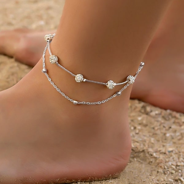Silver layered crystal anklet on a womans ankle