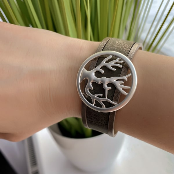 Silver tree of life leather cuff bracelet on a woman's wrist