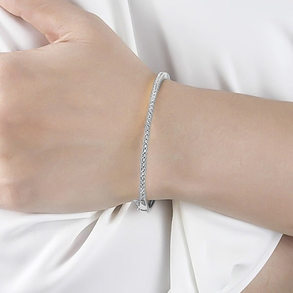 Silver zirconia bangle bracelet on a woman's wrist
